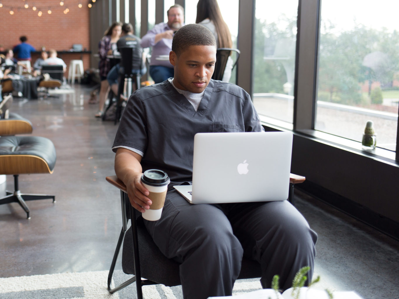 Nursing student in a coffee shop looking at a laptop