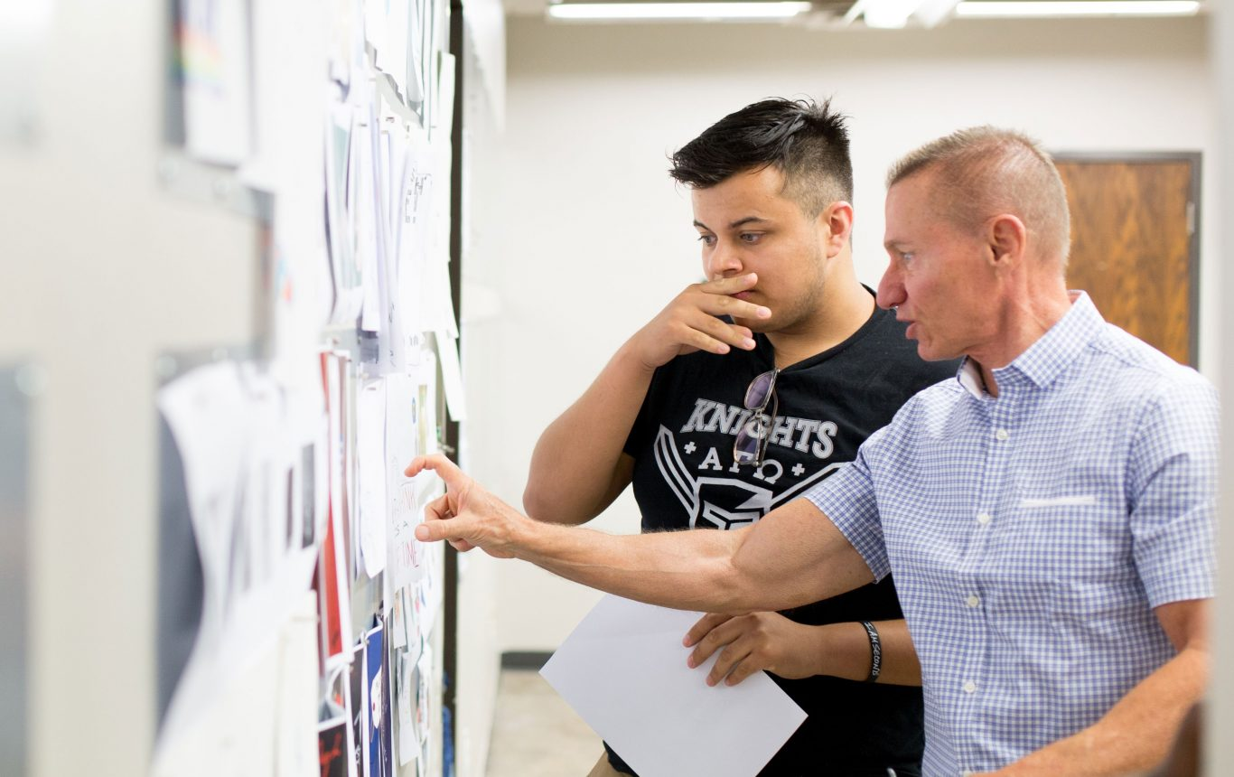 Professor and student reviewing design work