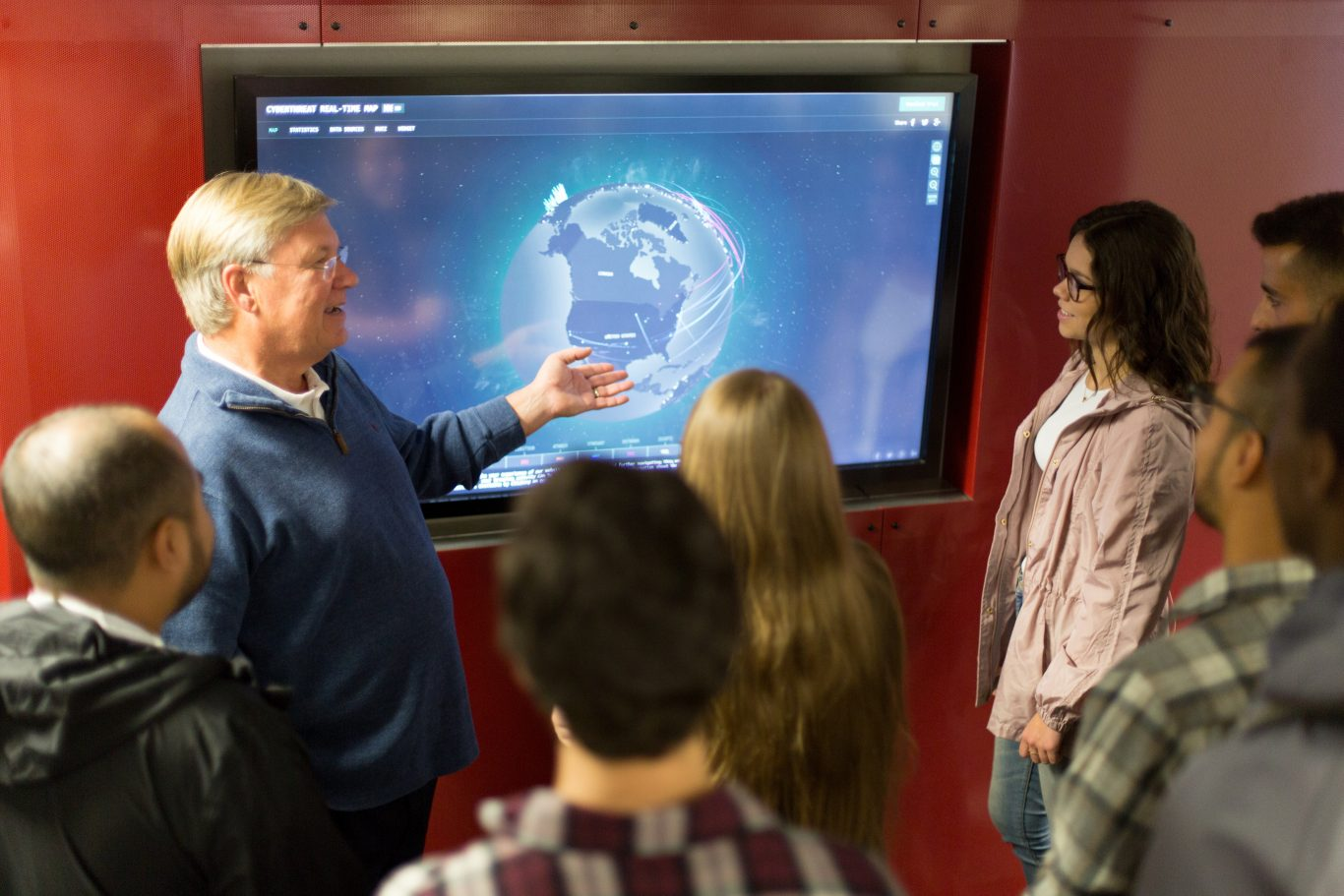 Professor and students at a display screen