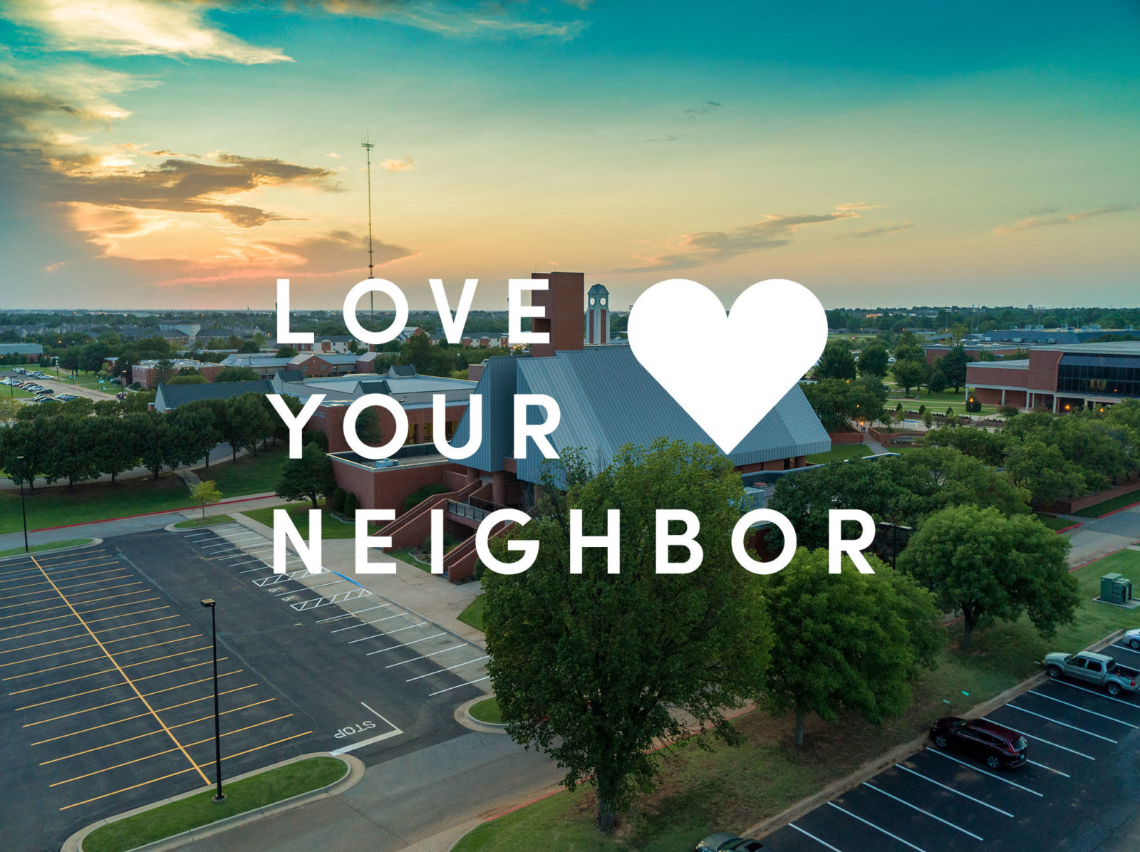drone shot of campus with Love your neighbor  text
